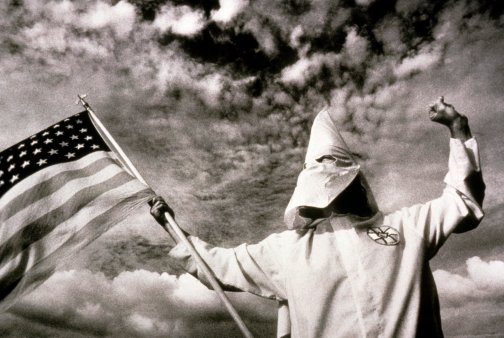 A Ku-Klux Klan member in Tennessee holds the American Flag.
