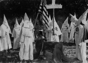 1st November 1922:  Members of American white supremacist secret society the Ku Klux Klan ceremonially initiate a new recruit at a meeting.  (Photo by Topical Press Agency/Getty Images)